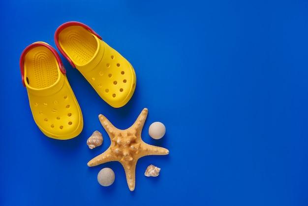 Chaussons De Plage Avec étoiles De Mer Et Coquillages Sur Bleu. Mise à Plat. Vue De Dessus. Photo Premium