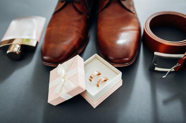 Chaussures en cuir marron, ceinture, parfum et bagues dorées. Photo Premium