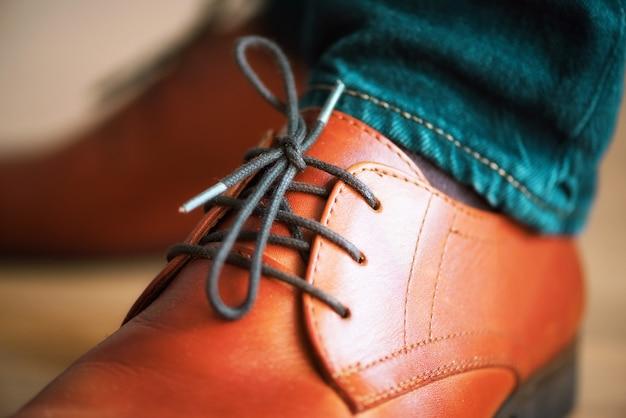 Chaussures en cuir marron homme d'affaires avec lacets sur un parquet en bois. concept de style et de mode. Photo Premium