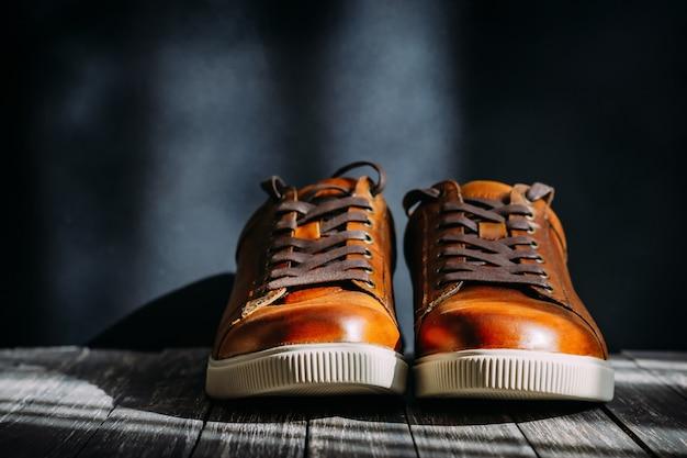Chaussures en cuir marron pour hommes avec lacets sur fond en bois foncé Photo Premium