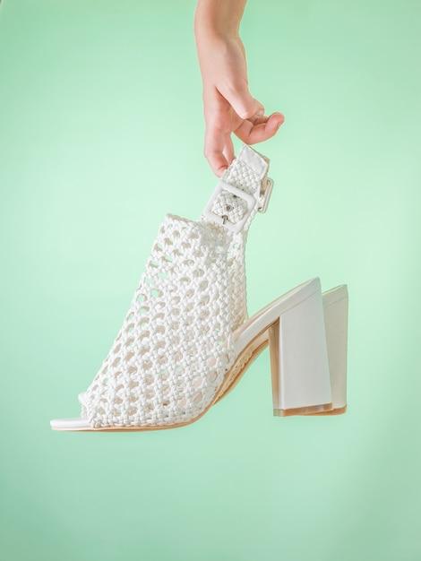 Chaussures D'été à La Mode Pour Femmes Blanches Dans La Main D'un Enfant Sur Fond Vert. Chaussures D'été En Cuir Pour Femmes. Photo Premium