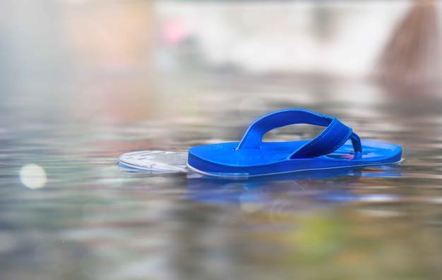 Chaussures flottant sur la rue inondée et après la pluie. Photo Premium