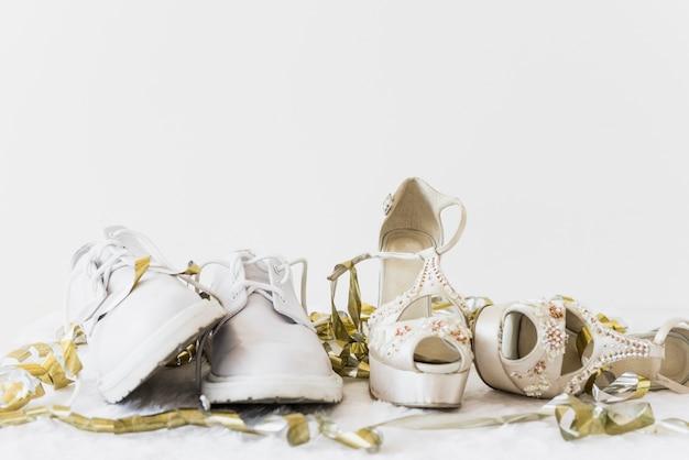 Chaussures De Mariage Blanches Et Talon Haut D'élégance Avec Des Banderoles Dorées Sur Fond Blanc Photo gratuit