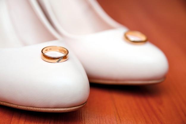 Chaussures de mariage blanches traditionnelles avec des anneaux sur bois. Photo Premium
