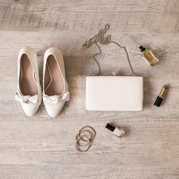 Chaussures de mariée blanche; parfum; rouge à lèvres; chouchous; embrayage et bandes de cheveux sur fond en bois Photo gratuit