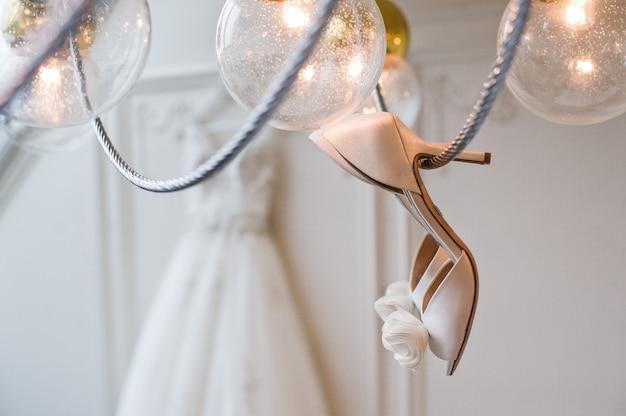 Les chaussures de la mariée sont suspendues au lustre à l'intérieur d'un hôtel de luxe Photo Premium