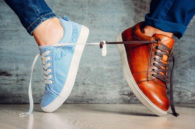 Les chaussures pour hommes et pour femmes vont dans des directions différentes et sont nouées de lacets. Photo Premium