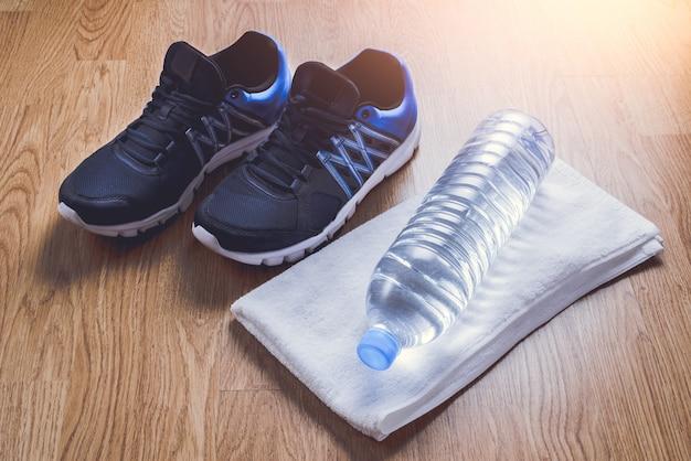 Chaussures de sport, eau, serviette sur fond en bois Photo Premium