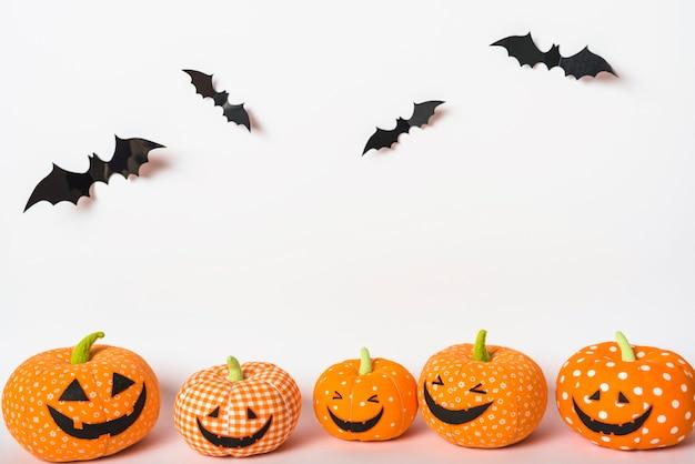 Des chauves-souris en papier sur des citrouilles-jouets Photo gratuit