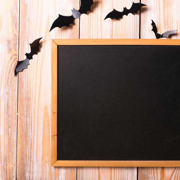 Chauves-souris en papier près du tableau Photo gratuit