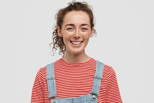 Cheerful Rousseur Jeune Femme Posant Contre Le Mur Blanc Photo gratuit