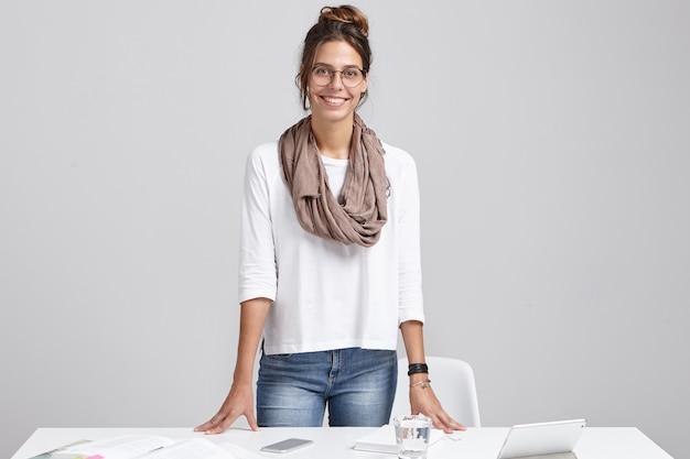 Cheerful Woman Designer D'intérieur Dans Des Verres, Se Dresse Sur Son Lieu De Travail, Photo gratuit