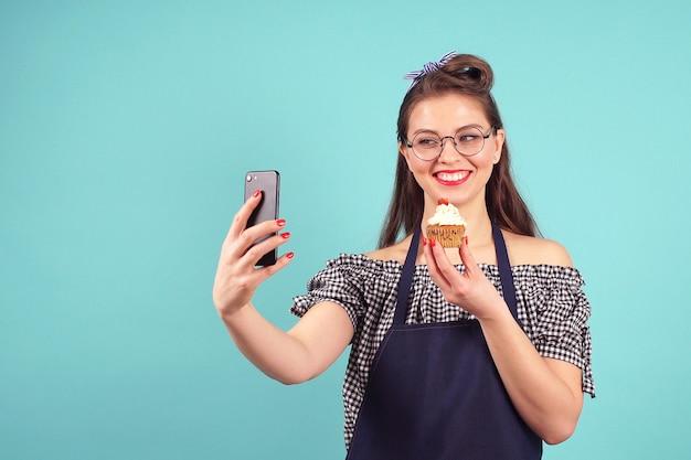 Cheerful Woman Pâtissier Fait Un Selfie Avec Un Petit Gâteau à La Main Photo Premium