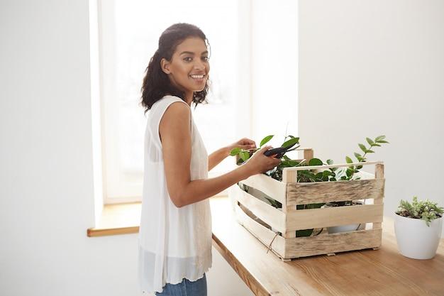 Cheerful Woman Smiling Prépare à Couper Les Tiges Des Plantes Sur Mur Blanc Et Fenêtre Photo gratuit