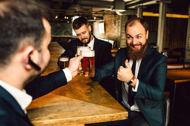 Cheerful Young Businessmen S'asseoir à Table. Ils Tiennent Des Tasses D'ours. Le Gars Barbu Tient Le Grand Pouce Vers Le Haut. Photo Premium