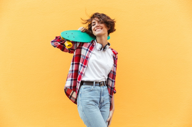 Cheerful Young Teenage Girl Holding Skateboard Sur Ses épaules Photo gratuit