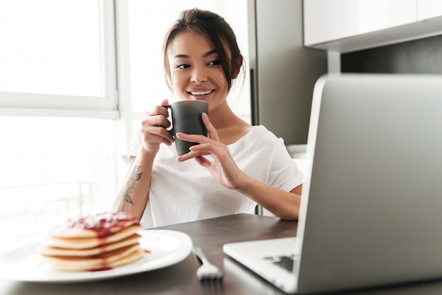 Cheerful Young Woman Sitting At The Kitchen Using Laptop Photo gratuit