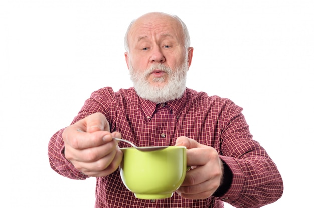 Cheerfull senior homme avec une tasse verte et une cuillère à café. Photo Premium