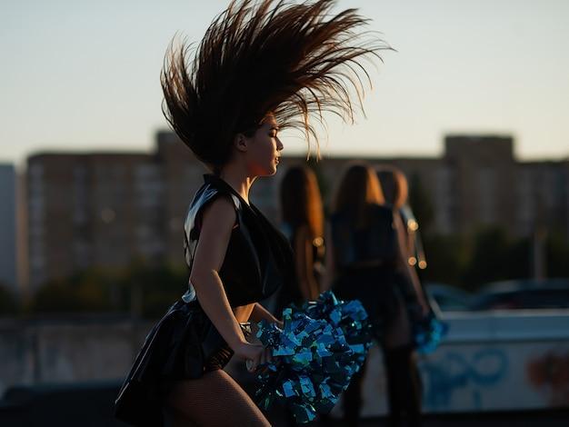 Cheerleaders dansant sur le toit au coucher du soleil contre le paysage de la ville Photo Premium