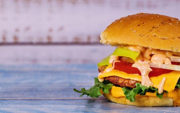 Cheeseburger avec du fromage fondu sur une table blanche. Photo Premium