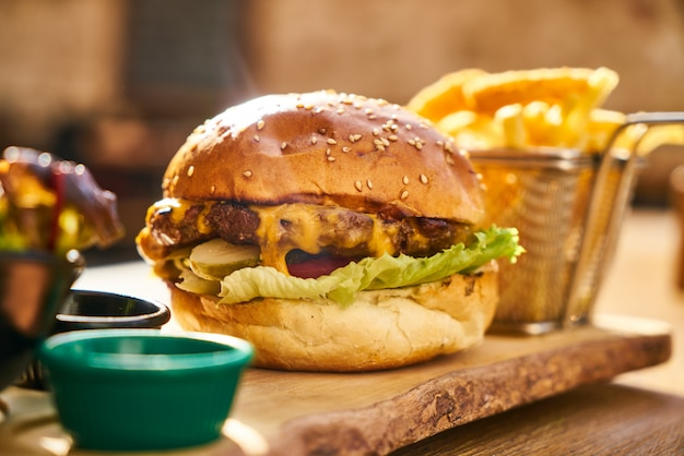 Cheeseburger avec des frites sur la table en bois Photo Premium