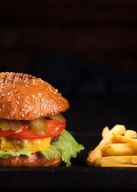 Cheeseburger savoureux avec des frites Photo gratuit