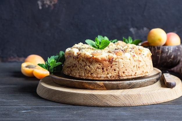 Cheesecake avec abricot et crumble, abricots frais et menthe. Photo Premium
