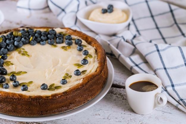 Cheesecake aux bleuets, tasse de café et pudding Photo Premium