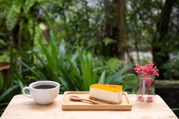 Cheesecake aux fruits de la passion et une tasse de café chaud sur un plateau et une table en bois Photo Premium