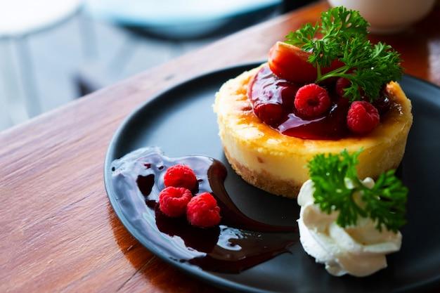 Cheesecake fait maison avec des baies fraîches et de la menthe au dessert Photo Premium