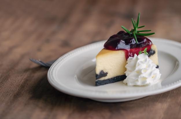 Cheesecake à la myrtille new york et crème fouettée boulangerie maison pour le gâteau d'anniversaire ou un café. Photo Premium