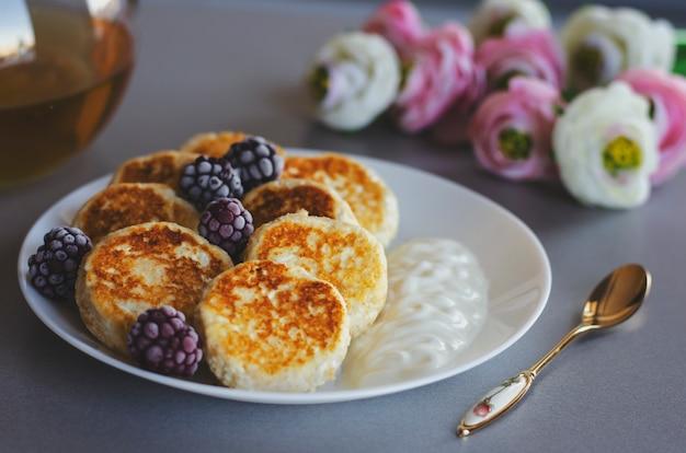 Cheesecakes from cottage cheese sur table grise avec une cuillère à thé et des fleurs Photo Premium