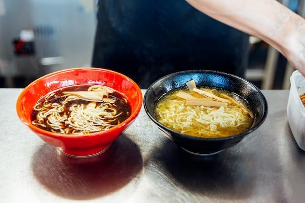 Chef ajoutant des ingrédients dans les nouilles ramen pour faire des ramen au miso et au shoyu. Photo Premium