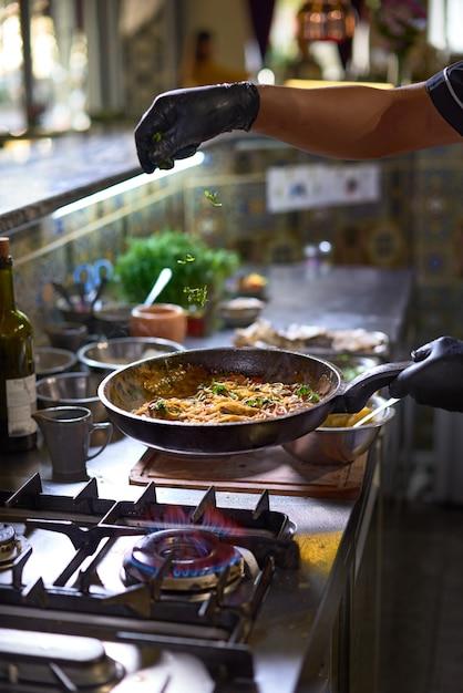 Le chef ajoute des légumes verts frais dans une poêle, des tomates et des huîtres. Photo Premium