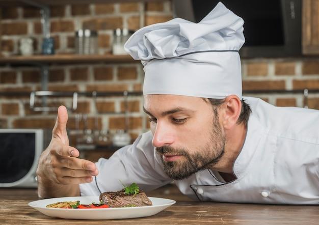 Chef appréciant l'arôme de la nourriture servie sur la plaque Photo gratuit