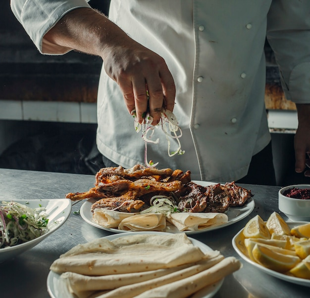 Le Chef Arrose Les Rondelles D'oignon Sur Une Plaque De Brochette Avec Du Poulet, De L'agneau, Des Pains Plats Photo gratuit