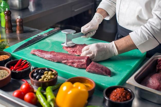 Chef Attendrir Steak Avec Attendrisseur De Viande Sur Une Planche à Découper Photo gratuit