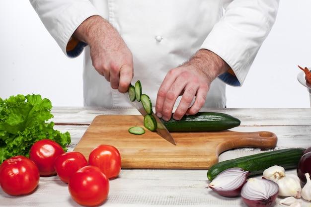 Chef Coupant Un Concombre Vert Dans Sa Cuisine Photo gratuit