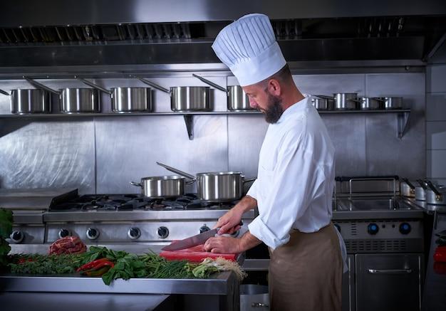 Chef couper la viande dans la cuisine du restaurant Photo Premium