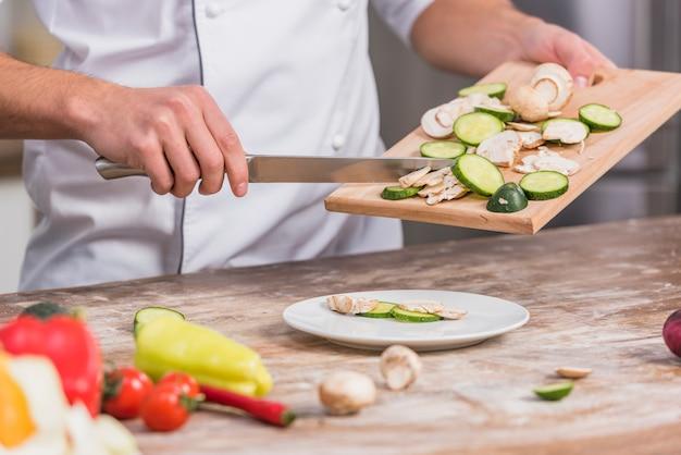 Chef en cuisine cuisiner avec des légumes Photo gratuit