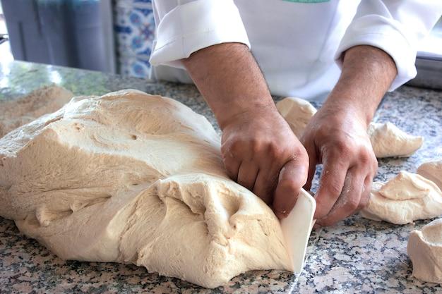 Chef cuisinier travaille avec une pâte à la levure Photo Premium