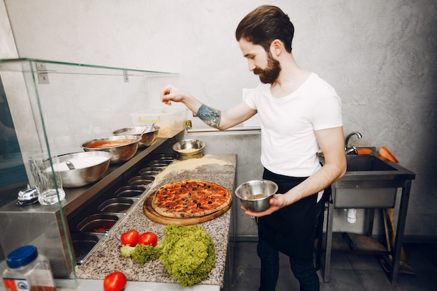 Chef dans la cuisine prépare une pizza Photo gratuit