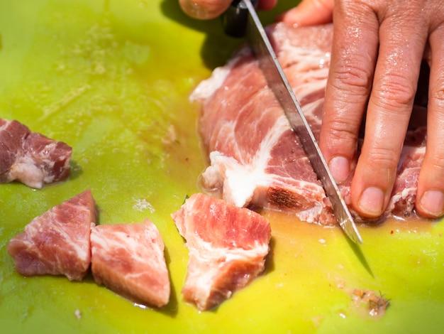 Chef découpant la viande sur une planche à découper Photo gratuit