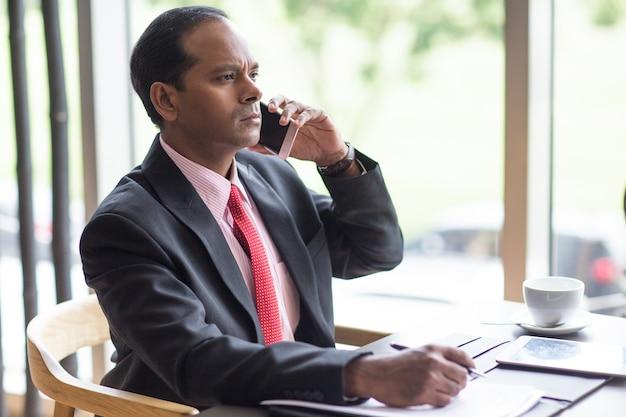 Chef d'entreprise sérieux appelant au téléphone au café Photo gratuit