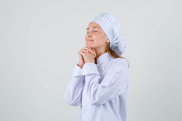 Chef Féminin étayant Le Menton Sur Les Mains Jointes En Uniforme Blanc Et à La Recherche D'espoir. Photo gratuit