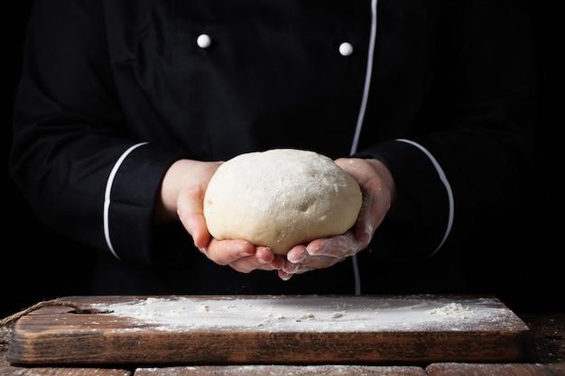 Chef féminin tenant la pâte à la levure dans ses mains sur fond noir. Photo Premium