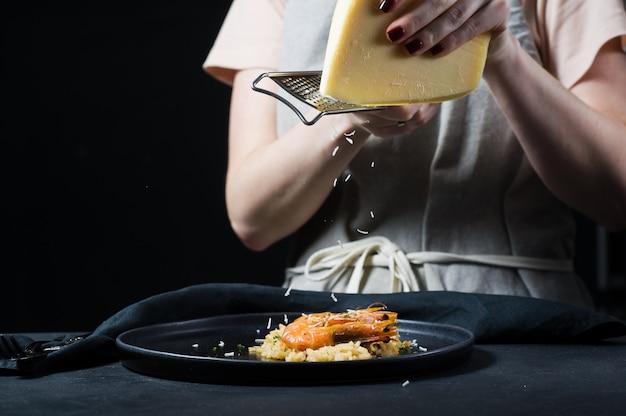 Le chef frotte du parmesan sur un risotto italien avec des crevettes sur une plaque noire. Photo Premium