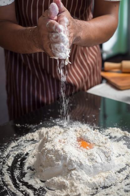 Chef hipster élégant main mélangeant le jaune d'oeuf, le sucre et la farine pour faire du pain sur le beau fond Photo Premium