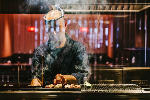 Le chef japonais yakitori fait griller du poulet mariné au gingembre, à l'ail et à la sauce soja avec beaucoup de fumée. Photo Premium