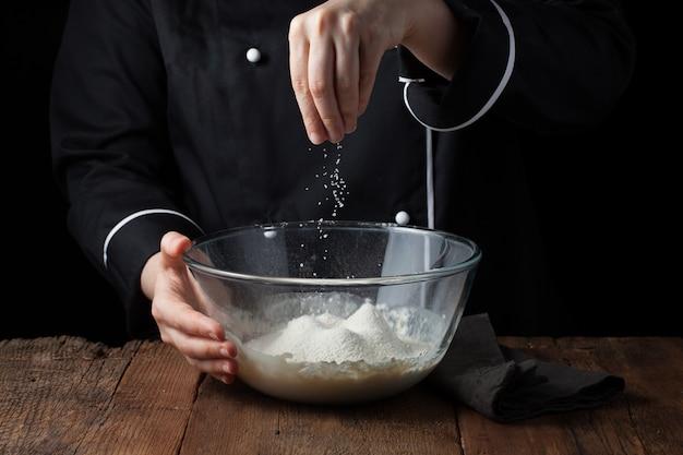 Chef mains saupoudrent de sel de mer sur la pâte crue. Photo Premium